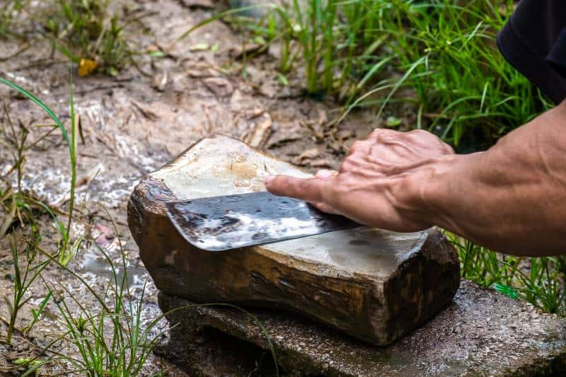 sharpening knife on stone outdoors
