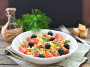 pasta salad with sauce and fork background