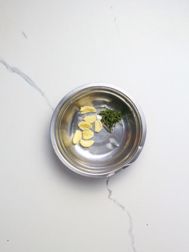 Garlic and rosemary in a mixing bowl