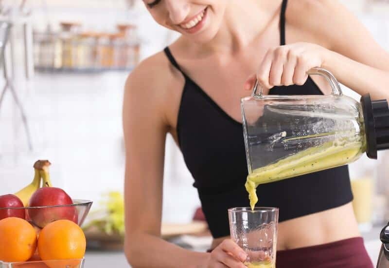 woman pouring smoothie from blender into glass
