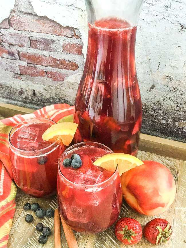 Berry peach sangria in pitcher and glasses
