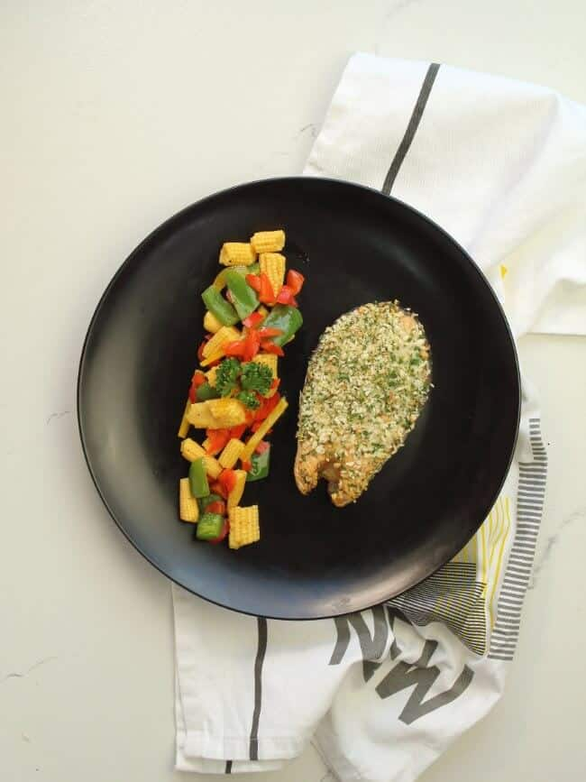 herb crusted baked salmon on black plate