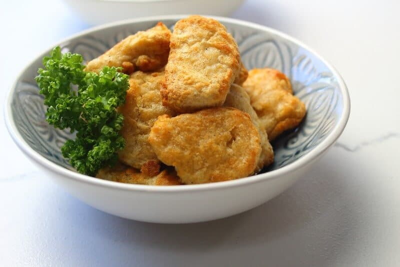 Golden brown chicken nuggets in a serving bowl