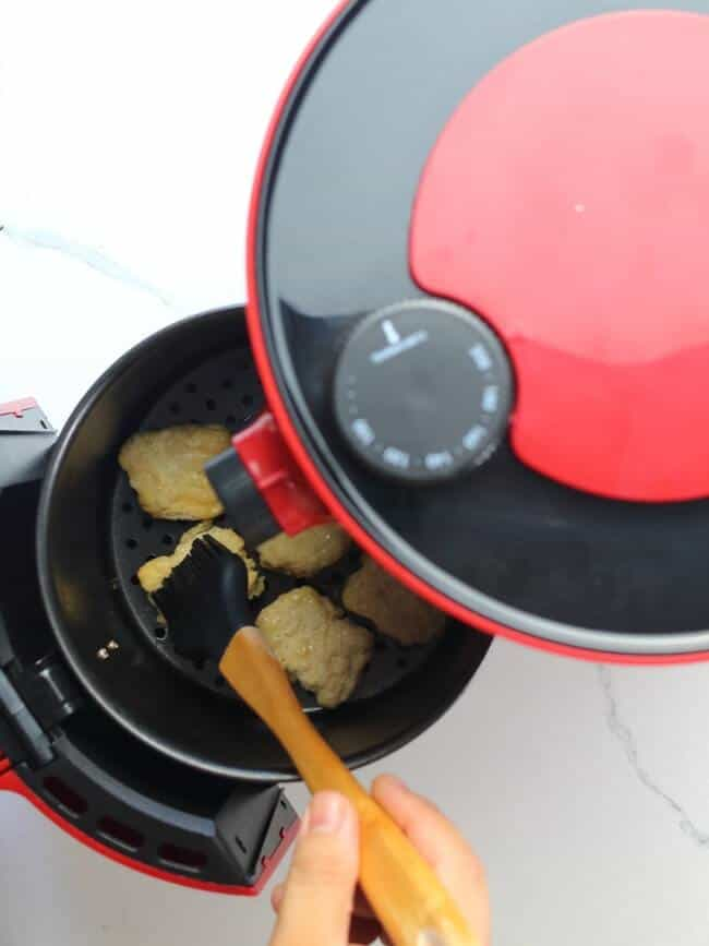 Brushing chicken nuggets with oil