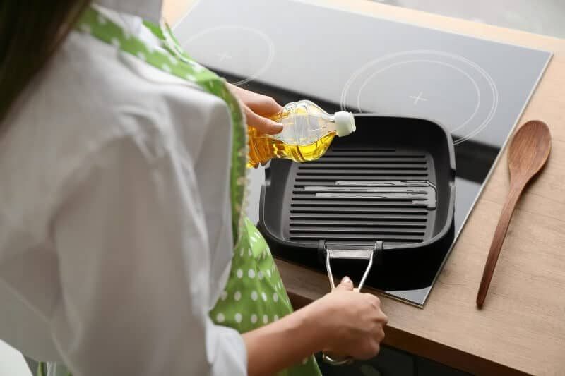 Woman Pouring Oil Onto Grill Pan