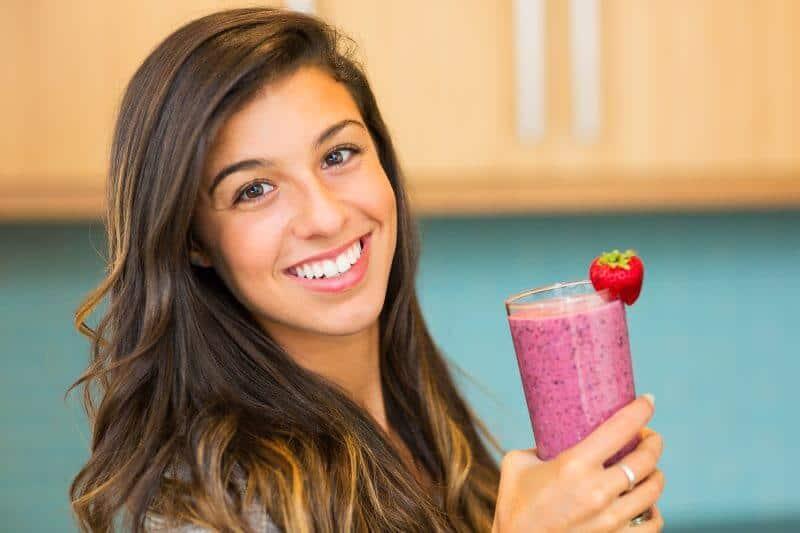 girl holding strawberry smoothie