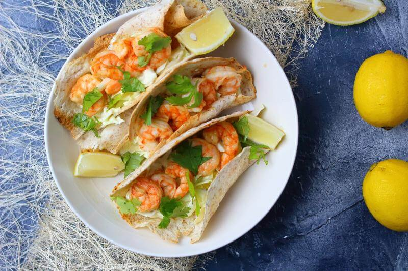 shrimp tacos with lemons in the side