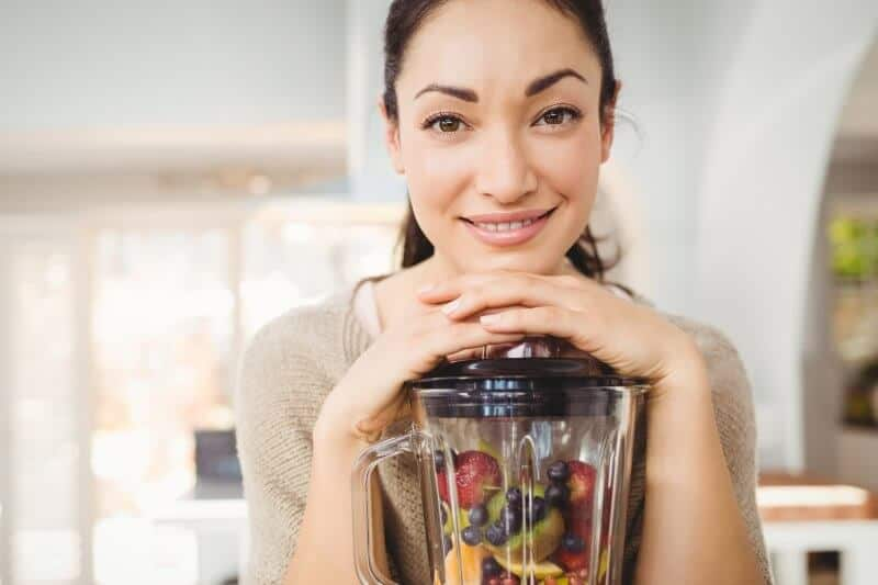 woman holding blender containing fruits