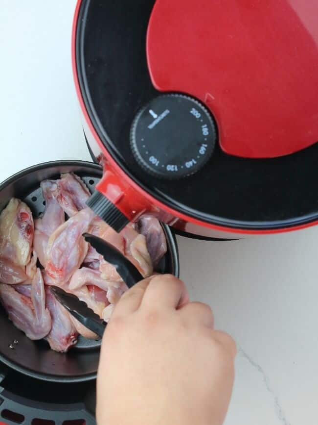 placing chicken inside the air fryer
