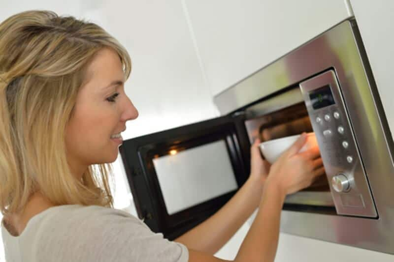 woman putting bowl in the microwave air fryer
