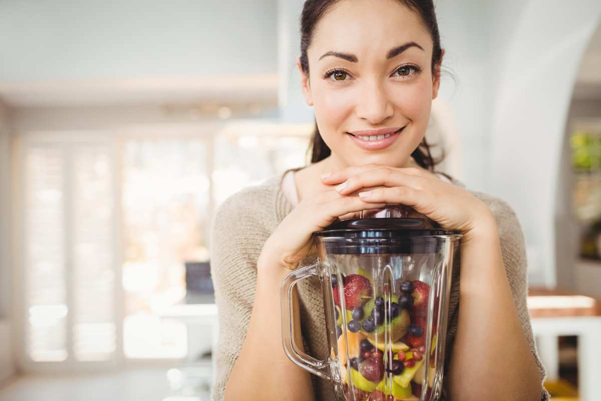 woman with blender containing mixed fruits