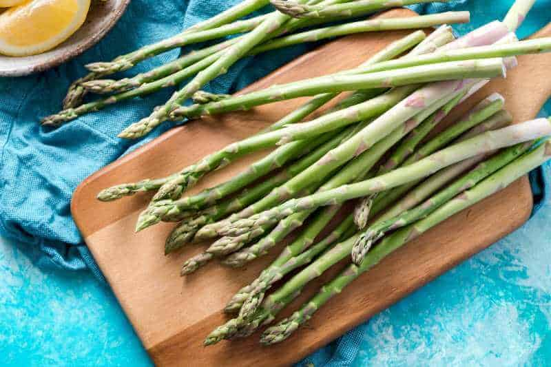 fresh asparagus on chopping board