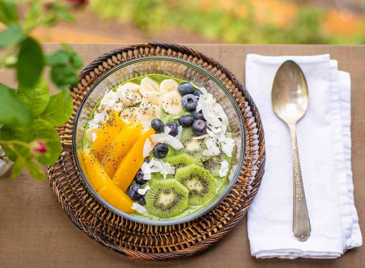 green smoothie bowl topped with fresh fruits