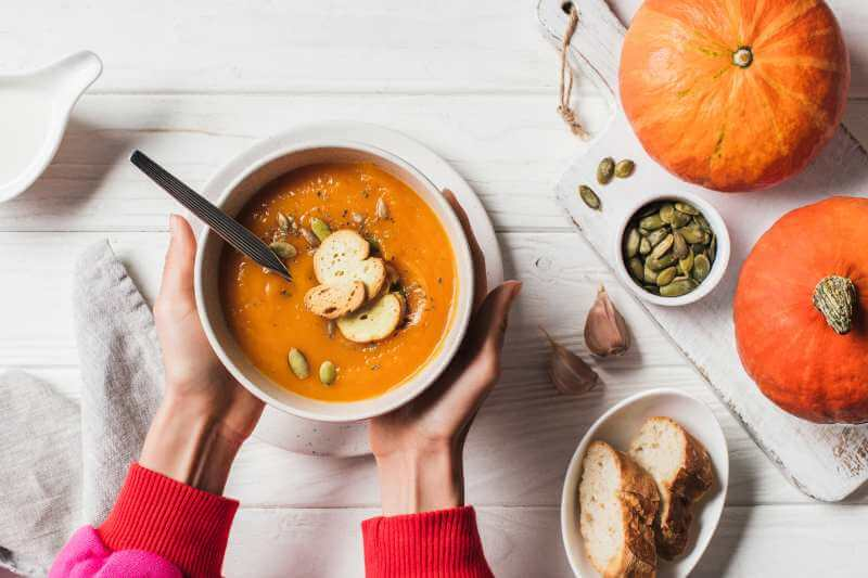 pumpkin soup topped with seeds and bread