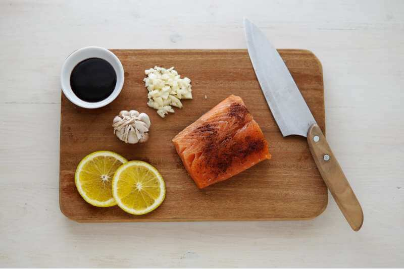 sauce with fish and lemon slices on chopping board