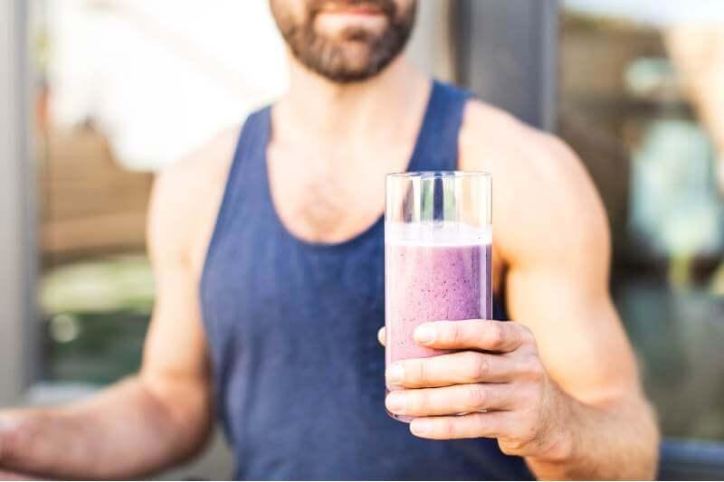 man enjoying a glass of smoothie