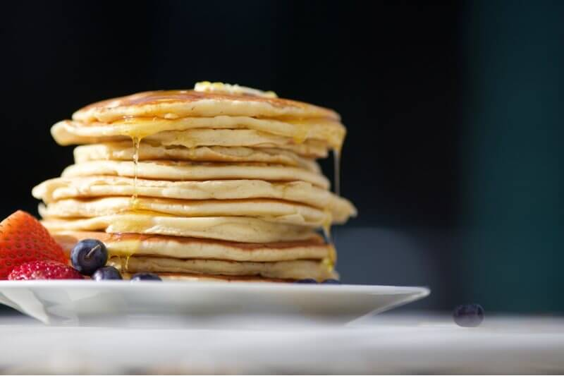 syrup dripping on stack of pancakes