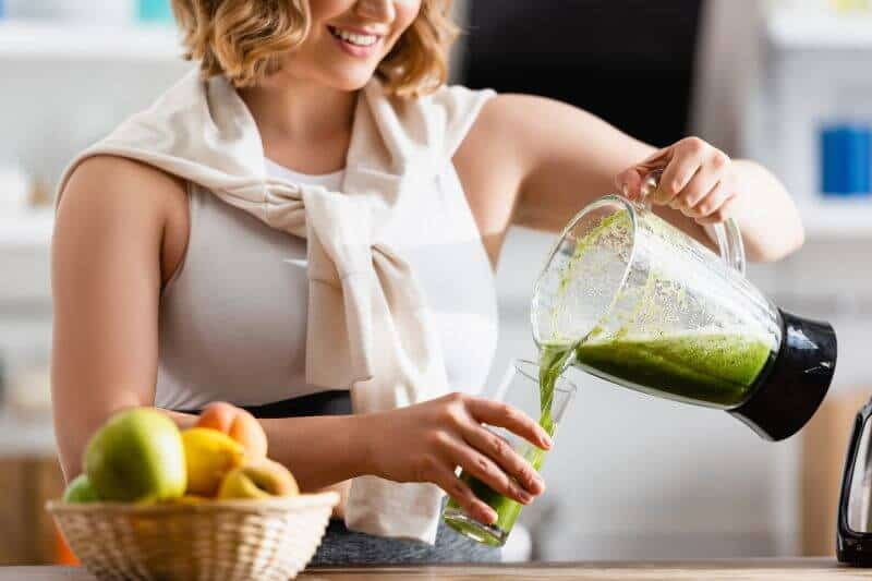woman pouring smoothie on a glass