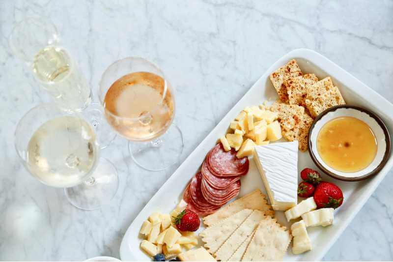 salami cheese and wine on white plate