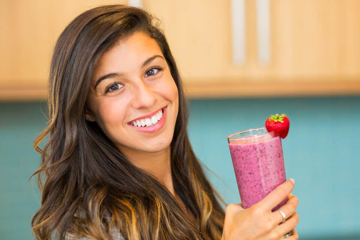 smiling woman holding a glass of smoothie