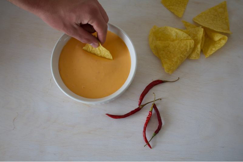 dipping nacho chips in melted cheese